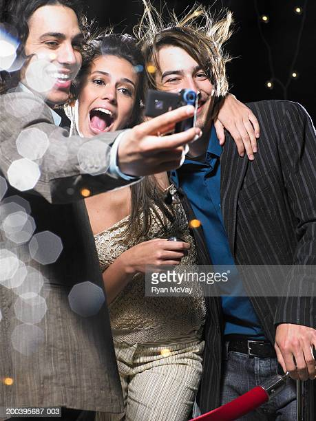 Young man taking self portrait with young woman and man, behind rope