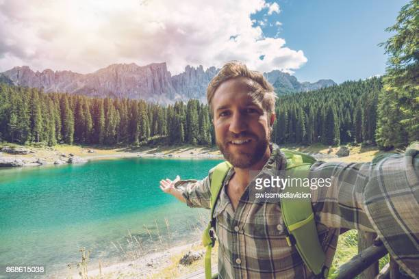 young man taking selfie at lake carezza, italy - wonderlust stock pictures, royalty-free photos & images