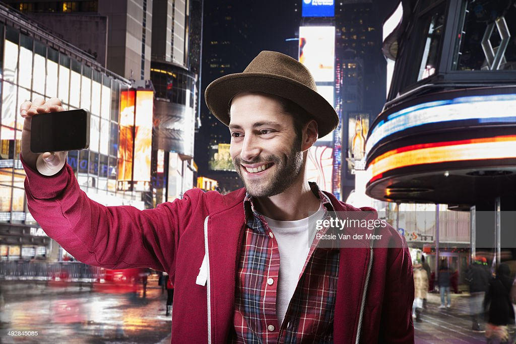 Young man taking selfie in city square at night. : Stock Photo