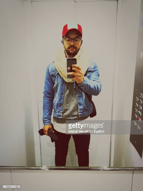 young man taking selfie in elevator mirror reflection - mirror selfie stock pictures, royalty-free photos & images
