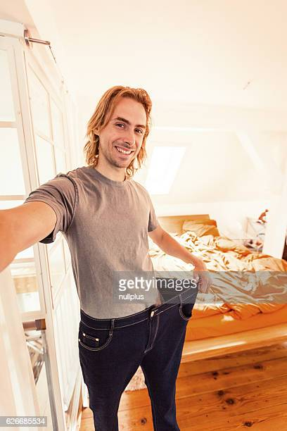 Young man taking selfie showing weight loss