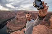 Young man taking selfie with action camera at the horseshoe bend in Arizona, USA