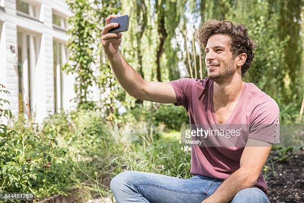 Young man taking selfie with cell phone in garden