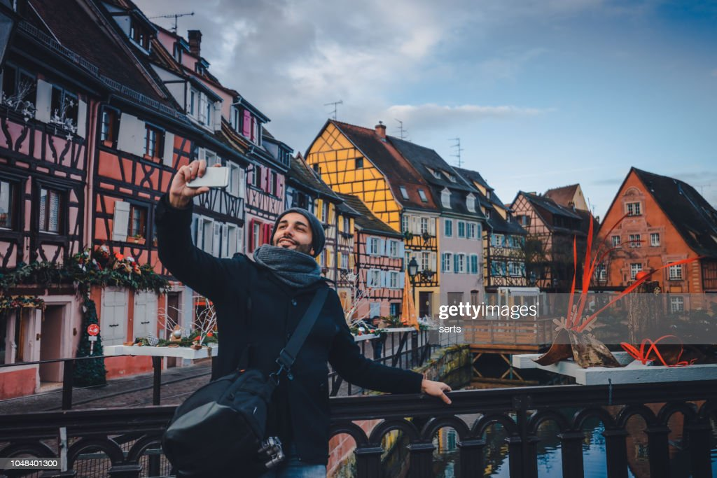 Young man taking selfie with smartphone in Colmar, France : Stock Photo