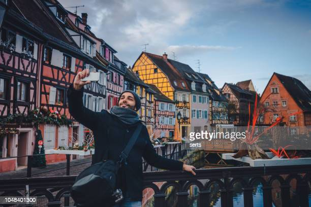 young man taking selfie with smartphone in colmar, france - colmar stock photos and pictures
