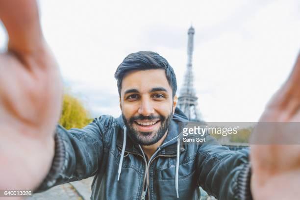 jeune homme prenant un selfie avec smartphone - essayer de marquer photos et images de collection
