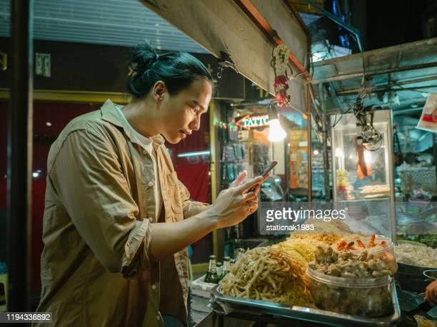 カオサンロードでストリートフードパッドタイで自分撮りを取る若い男。 - タイ文化 ストックフォトと画像