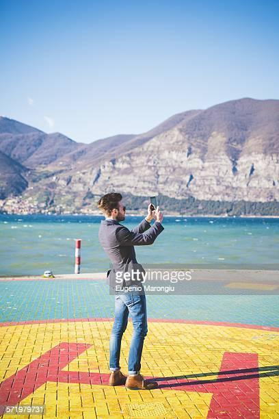 Young man taking smartphone photographs from helipad, Rovato, Brescia, Italy