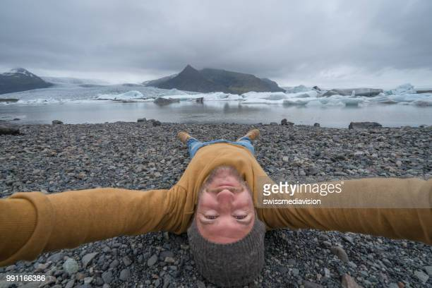 Young man taking upside down selfie with glacier lake, icebergs floating on water