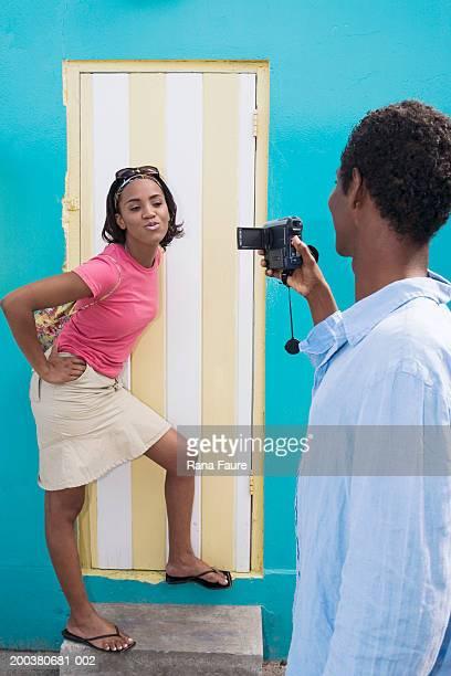 Young man taking video of woman puckering lips in doorway