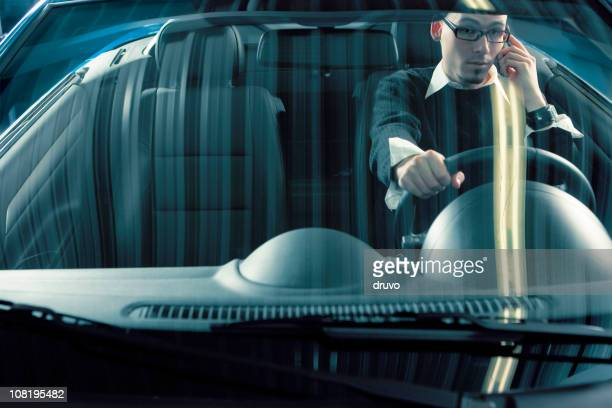 Young Man Talking on Cell Phone and Driving Sports Car