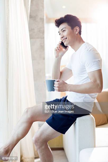 Young man talking on cell phone at home