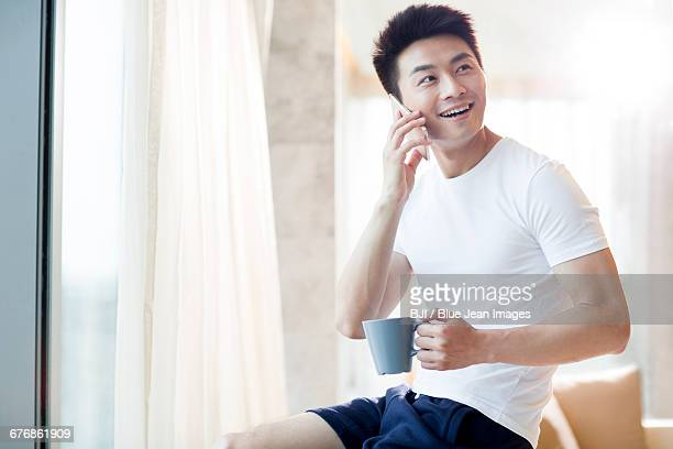 young man talking on cell phone at home - short sleeved stock photos and pictures