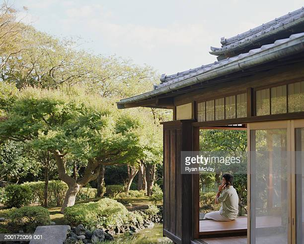Young man talking on cell phone in room overlooking garden, rear view