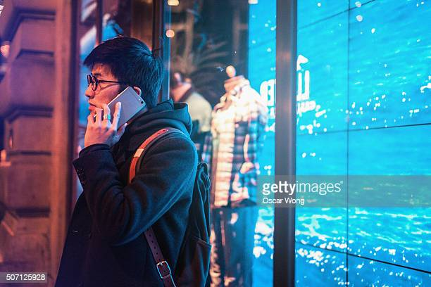 Young man talking on cell phone next to a fashion store