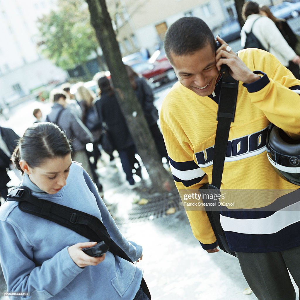 Young man talking on cell phone next to young woman dialing cell phone outside. : Stockfoto
