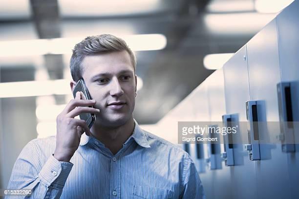 young man talking on mobile phone in locker room, freiburg im breisgau, baden-württemberg, germany - sigrid gombert stock-fotos und bilder