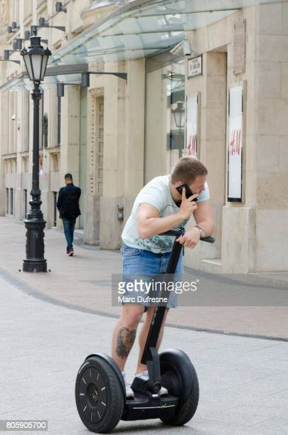 young man talking on mobile phone while on segway in street of downtown of budapest during summer day - segway stock pictures, royalty-free photos & images