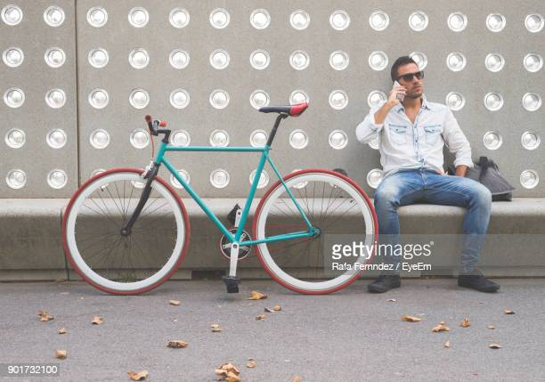 Young Man Talking On Mobile Phone While Sitting By Bicycle