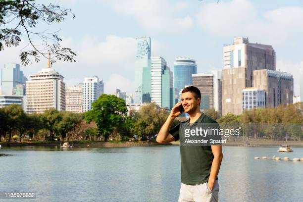 young man talking on mobile phone with bangkok skyline background - polo shirt stock photos and pictures