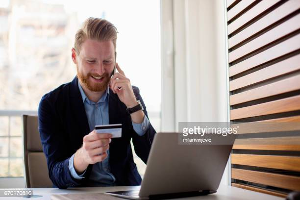 Young man talking on phone and doing online purchase