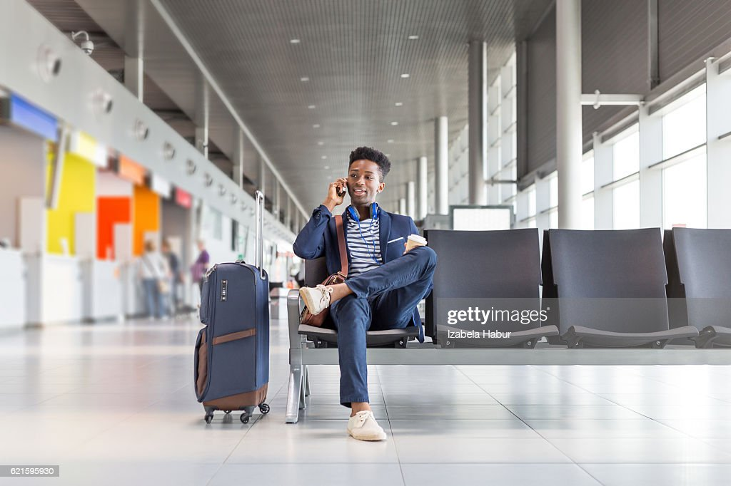 Young man talking on phone at airport lounge : Foto de stock