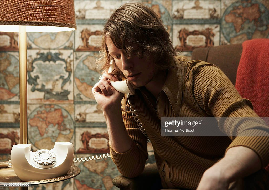 Young man talking on phone in room : Stock Photo