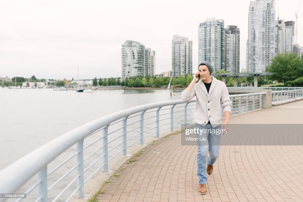 Young man talking on phone while walking along seawall, Yaletown, Vancouver, Canada : Stock Photo