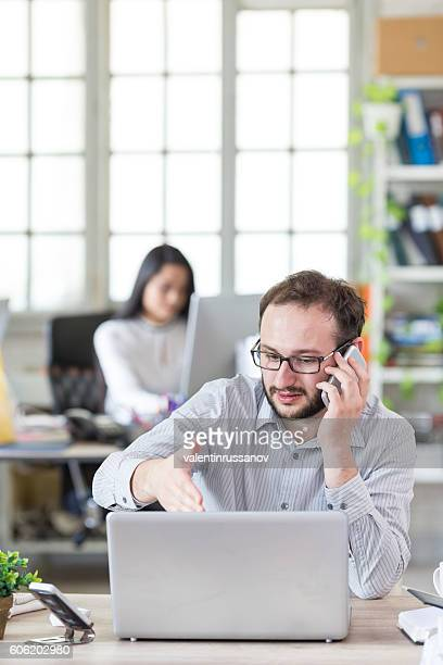 Young man talking on the phone at the office
