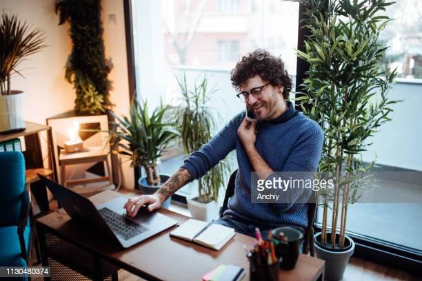 jonge man praten over de telefoon in zijn kantoor aan huis - voip stockfoto's en -beelden