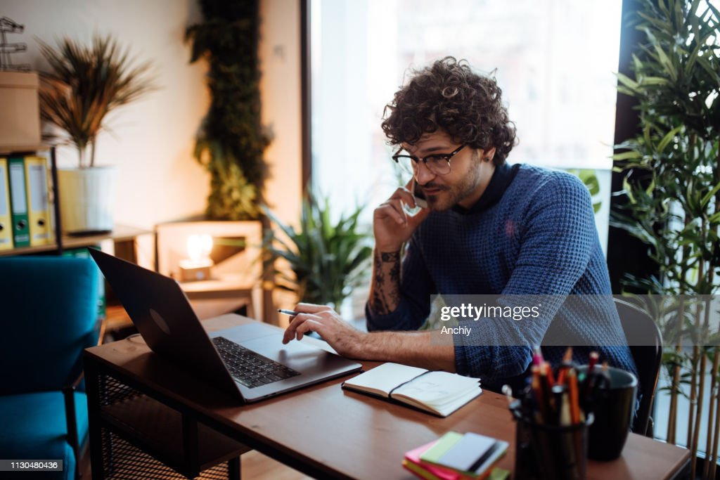 Young man talking on the phone in his home office : Stock Photo