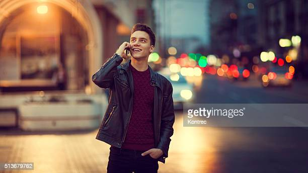 Young man talking on the phone outdoors at nighttime