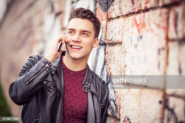 young man talking on the phone outdoors - one young man only stock pictures, royalty-free photos & images
