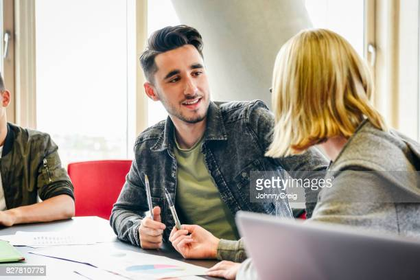Young man talking to female student in classroom