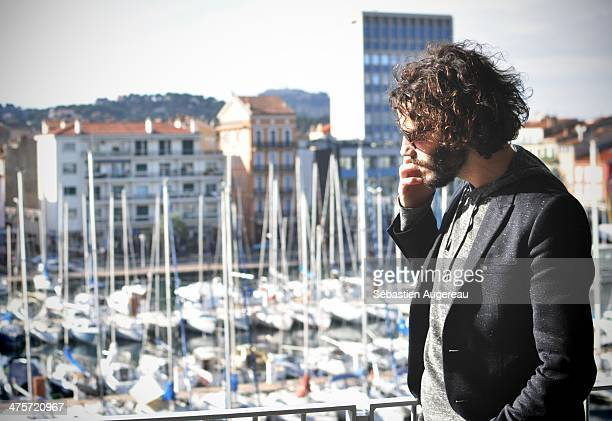 Young man talking with a phone, in a balcony with boats in background. Long dark hair fashioned man.