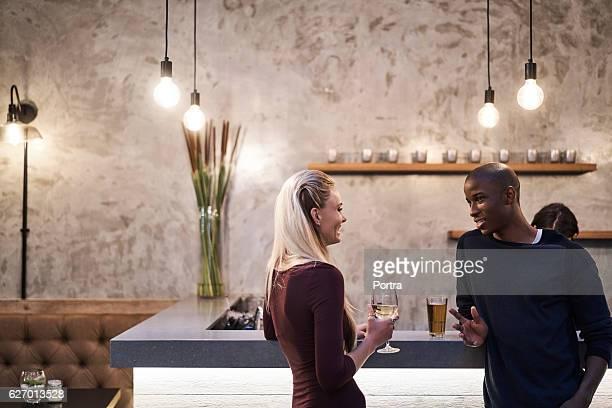 Young man talking with woman at bar counter