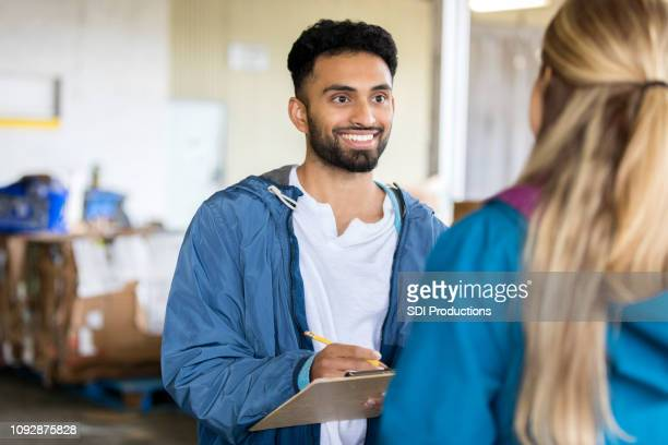 young man talks to women in food bank - charity benefit stock pictures, royalty-free photos & images