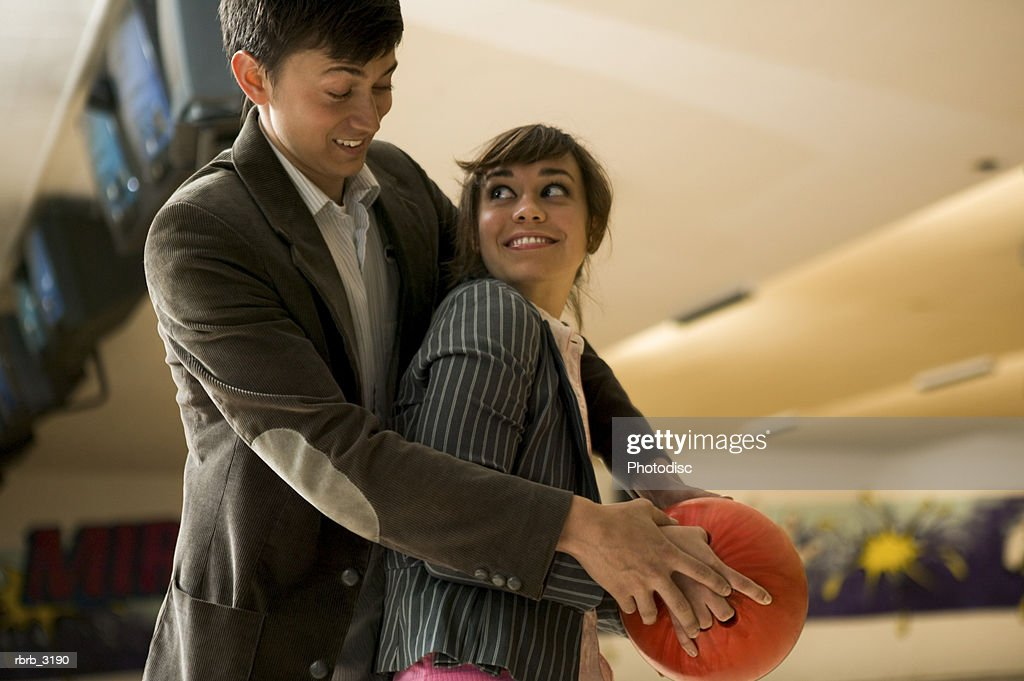 Young man teaching a young woman how to bowl : Foto de stock