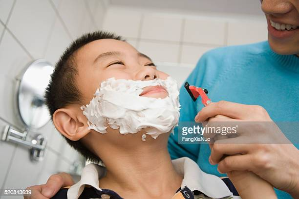 Young man teaching boy (8-9) to shave, smiling