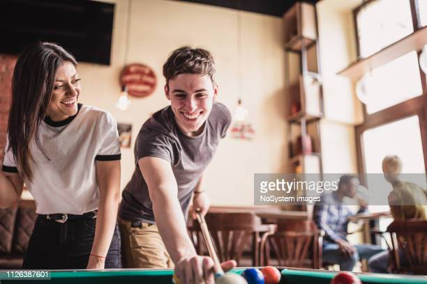 junger mann lehrt seine freundin, billard zu spielen - poolbillard billard stock-fotos und bilder