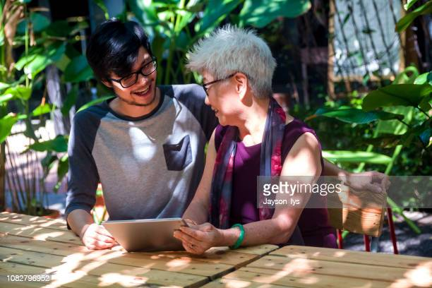 young man teaching senior lady using tablet - showing respect stock pictures, royalty-free photos & images