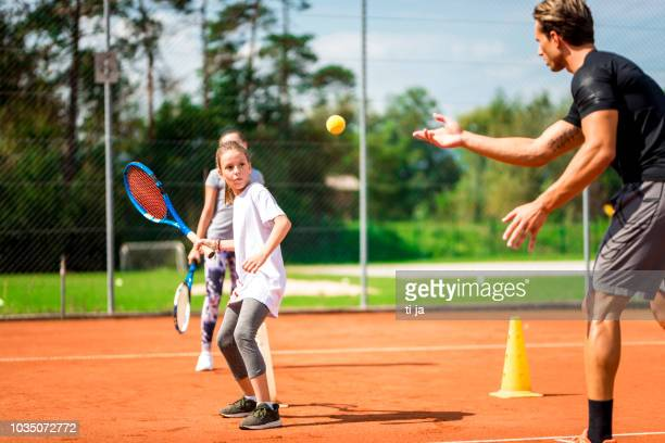 young man teaching two girls playing tennis - tennis stock pictures, royalty-free photos & images