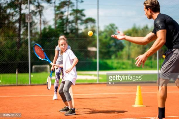 junger mann zwei mädchen spielen tennis unterricht - tennis stock-fotos und bilder