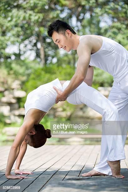 Young man teaching woman yoga