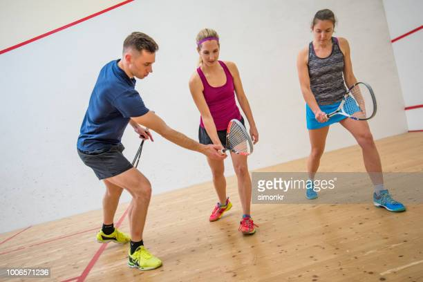 young man teaching young women how to hold squash racket - squash sport stock pictures, royalty-free photos & images