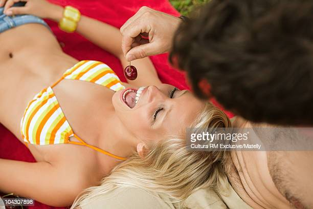 Young man teasing girl with a cherrie