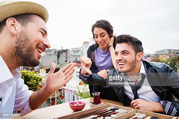 Junger Mann seine Freundin verwirrst während Partie backgammon tavla