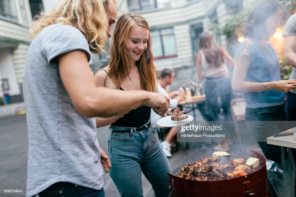 "Young Man Tending Barbecue Serving Food To His Friends""n : Stock Photo"