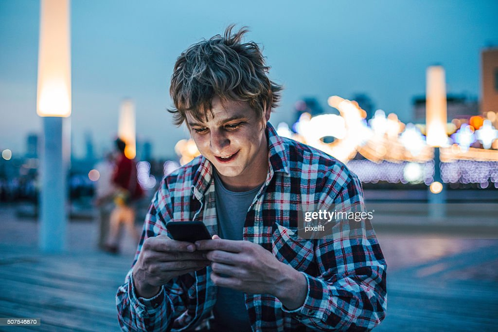 Young man text messaging at urban scene : Stock Photo