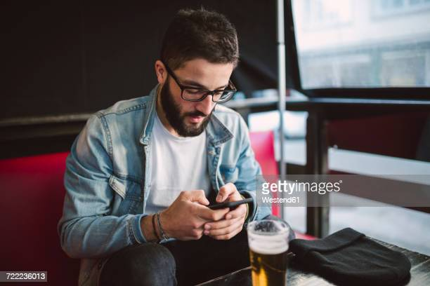 young man text messaging in a pub - one man only stock pictures, royalty-free photos & images